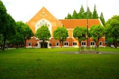 Europeiskt stilhus för orange tegelsten bak en grön gräsmatta arkivbild