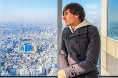 Europeiskt turist- anseende vid fönstret och se ut fönstret Panoramautsikt av Tokyo royaltyfri fotografi