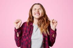 Europejczyk radujący się szczęśliwy żeński zwycięzca z przyjemnym uśmiechem, zaciska pięści i zęby, radują się zwycięstwo wielki  fotografia stock