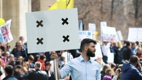 Europejscy ludzie przy demonstracją Mężczyzna krzyczy w cygarniczkę z sztandarem zbiory