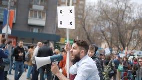 Europejscy ludzie przy demonstracją Mężczyzna krzyczy w cygarniczkę z sztandarem zbiory wideo
