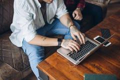 Europejska homoseksualna męska para wpólnie pije kawę i ogląda laptop wydaje czas zdjęcie stock