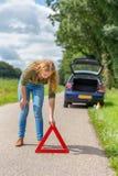 Europejska kobieta umieszcza zagrożenie ostrzegawczego trójboka na drodze zdjęcia royalty free