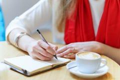 Europejska kobieta z czerwonym szalikiem pisze piórem coś w notepad blisko białej filiżanki kawy na stole Fotografia Stock