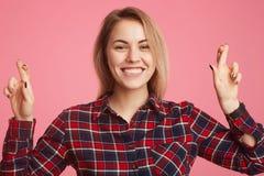 Europejska uśmiechnięta kobieta ubierał w w kratkę koszula, krzyży palce jak robi pragnący życzenie, nadzieje mieć szczęście przy obraz stock