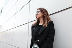 Europejski miastowy młoda kobieta modniś w modnym czarnym żakiecie w koszulce w ciemnych modnych okularach przeciwsłonecznych w c obrazy royalty free
