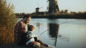 Europejski ojciec i syn siedzimy wpólnie na jeziornym molu Chłopiec trzyma ręcznie robiony połowu sprzęt rodzinni szczęśliwi zwią zbiory
