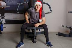 Europejski sportowiec, jest ubranym Santa kapelusz, siedzi na symulancie, iść na piechotę szeroki w oddaleniu i śmia się, Zdjęcia Stock