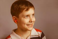 Europeo-mirada del muchacho de diez años que escucha Foto de archivo