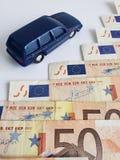 Europese bankbiljetten en cijfer van een auto in donkerblauw stock fotografie