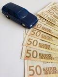 Europese bankbiljetten en cijfer van een auto in donkerblauw stock foto's