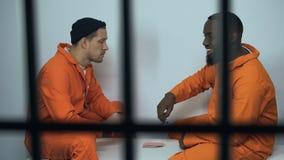 Europese en Afrikaans-Amerikaanse medebewonersspeelkaarten in cel, onwettige activiteit stock videobeelden