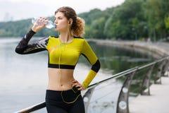 Europese geschiktheidsvrouw met speler en geel hoofdtelefoons drinkwater van fles Royalty-vrije Stock Afbeelding