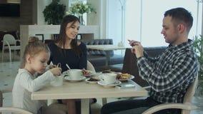 Europese jonge familie die diner hebben bij restaurant Vader die op zijn smartphone schieten terwijl kelners dienende lijst stock videobeelden