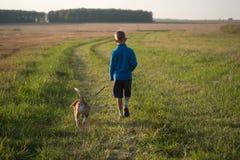 Europese jongen die met een Brak op een gang lopen stock fotografie