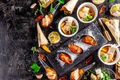 Europese keuken voorgerecht voor wijn op een zwarte achtergrond Pastei, minisalade, canape, overzeese producten, zalm en mosselen stock afbeelding