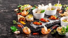 Europese keuken voorgerecht voor wijn op een zwarte achtergrond Pastei, minisalade, canape, overzeese producten, zalm en mosselen stock fotografie