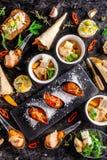 Europese keuken voorgerecht voor wijn op een zwarte achtergrond Pastei, minisalade, canape, overzeese producten, zalm en mosselen stock foto's