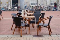 Europese koffielijsten en rieten stoelen op een baksteen-gelegde stadsstraat royalty-vrije stock fotografie