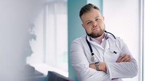 Europese medische artsenmens die wapens kruisen en camera bekijken stock videobeelden