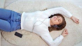 Europese tienervrouw die witte de wintersweater dragen die pret het luisteren muziek hebben die hoofdtelefoons met behulp van stock videobeelden