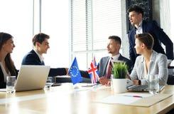 Europese Unie en van het Verenigd Koninkrijk leiders die handen op een overeenkomstenovereenkomst schudden stock foto