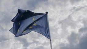 Europese Unie vlag die in de wind tegen een blauwe hemel golven Het concept patriottisme Langzame Motie stock video