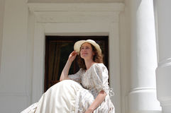 Europese vrouwenzitting in zonneschijn en wat betreft hoed in uitstekende kleding dichtbij paleis Royalty-vrije Stock Afbeeldingen