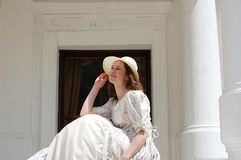 Europese vrouwenzitting in zonneschijn en wat betreft hoed in uitstekende kleding dichtbij paleis Stock Foto's