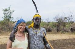 Europäische Frau und Mann von Mursi-Stamm in Mirobey-Dorf Mago Lizenzfreie Stockfotos