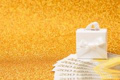 200 euroräkningar och gåvaask på guld- mousserande bakgrund Royaltyfri Foto