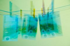 100 euroräkningar som hänger på en färgrik moneylaundring för clothline Arkivbilder