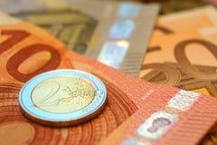 Eurorechnungen und ein Münzenmakro Stockfoto