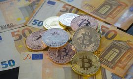 Euros and Bitcoin BTC coins on bills of euro banknotes. Worldwid Royalty Free Stock Photo