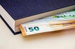 50 and 100 euros in a book on the table, close-up. 50 and 100 euros in a book on the table royalty free stock photos