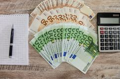100 and 50 euros, a calculator, a notebook and a pen on a wooden background. 100 and 50 euros, a calculator, a notebook and a pen royalty free stock photography