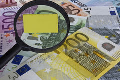 Euros with copy space. Euros (EUR) with a magnifying glass over a blank yellow note Royalty Free Stock Photos