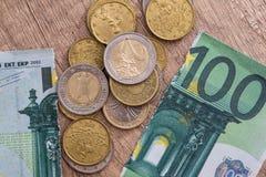 100 euros déchirés avec des pièces de monnaie Photographie stock