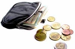 Euros dans la bourse noire et pièces de monnaie sur un fond blanc Image stock