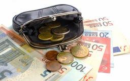 Euros dans la bourse noire et pièces de monnaie sur un fond blanc Photo stock
