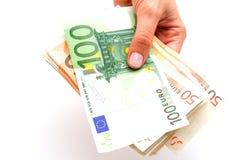 Euros dans les mains sur le fond blanc Photos stock