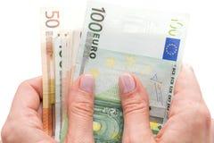 Euros in den Händen auf weißem Hintergrund Stockfotos