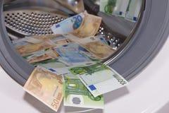 Euros dentro de la lavadora, concepto del blanqueo de dinero fotos de archivo