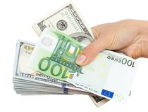 Euros and Dollars in hand on a white background.  Royalty Free Stock Images