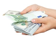 Euros and Dollars in hand on a white background.  Royalty Free Stock Photo