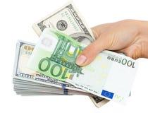 Euros et dollars à disposition sur un fond blanc Images libres de droits