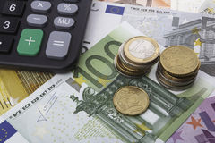 Euros (EUR) and a calculator. Business concept. Euro (EUR) notes, coins, and a calculator. Business concept Stock Photos