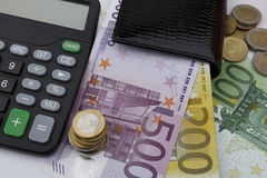 Euros (EUR) notes and coins. Business concept. Euros (EUR) notes and coins, together with a calculator and a black wallet Royalty Free Stock Images