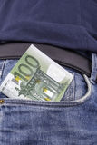 Euros (EUR) in a pocket. Euros (EUR) in the front pocket of a pair of  blue jeans. (100 Euro note Stock Image