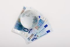 Euros and globe. Euros and glass globe on white background Stock Images